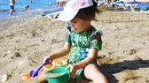 brinquedos : Little girl playing with childrens dishes on a sandy beach next to the sea.
