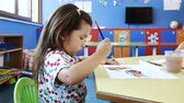ressam : Little cute girl draws a picture on white paper with watercolor paint in the childrens playroom (nursery). Stok Video