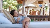 amusing : The little cute girl is resting, talking and eating on the soft seats of the gazebo. Stock Footage