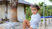 indicação : Little actress with a good imagination. Cute beautiful baby girl talking to herself, sitting on the beach under palm trees next to the gazebo. Stock Footage