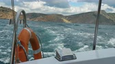 bílý : View from the side of a motor boat on the sea and mountains. The boat swings on the waves. Dostupné videozáznamy