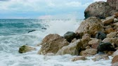 pedregulhos : Sea waves are breaking on a rocky shore. In the background is a blue cloudy sky. Evening time. Stock Footage