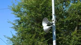 aviso : Loudspeakers fitted to make announcements on the street pole. In the background dense foliage of trees and blue sky. Close up.