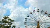 reuzerad : Colorful ferris wheel in an amusement park against the gray sky with clouds. View from afar. Stockvideo
