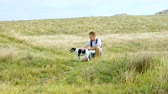 pooch : A young man walks with a dog along the sea coast. Cheerful smiling guy with a backpack on his shoulders stroking the dog. In the background meadow with dry grass. Strong wind blows.