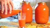 skřípat : Housewife pours freshly brewed tomato juice into a glass cup. Cooking and canning for the winter.