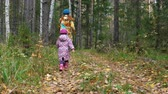 tendo : Mom and daughter are running along the path in the autumn forest.