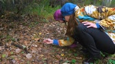 analık : Mom teaches her little daughter to pick mushrooms in the autumn forest.