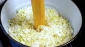 fermented : Cooking sauerkraut in an enamelled bucket. Squeezing the juice out of vegetables using a wooden pestle.