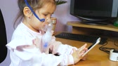 A pretty little girl sits in a chair at the computer desk, is treated with a nebulizer and uses a mobile phone. Vídeos