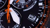 six : Close-up of a quartz wrist watch with a chronograph. Movement of the orange second hand.