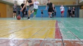 Basketball game. Teens train in the school old sports hall, throw the ball in the basket and run with the ball.