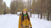 Girl tourist in orange winter clothes walking along a winter forest road with a backpack on her shoulders. Slow motion. Vidéos Libres De Droits