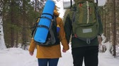 ladin : Tourists, a young man and a girl, walk along the winter forest path holding hands. Slow motion.