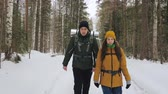 A young man and a girl are walking along a winter forest path with backpacks on their shoulders. Slow motion. Vidéos Libres De Droits