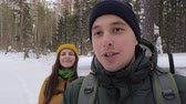 A young man, a tourist and a video blogger, is recording a video in the winter forest with his girlfriend. Slow motion.