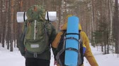 motivatie : Tourists, a young man and a girl, are walking along a winter forest path with backpacks on their shoulders and waving hands behind them. Slow motion.
