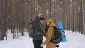 Tourists, a young man and a girl, are walking along a winter forest path with backpacks on their shoulders and waving hands behind them. Slow motion.