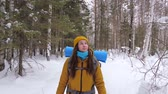 motivatie : Girl tourist in orange winter clothes walking along a winter forest path with a backpack on her shoulders. Slow motion.