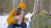 motivatie : Girl tourist in the winter snow-covered forest drinking tea from a thermos next to a backpack. Slow motion.
