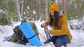 coberto : Girl tourist in the winter snow-covered forest drinking tea from vaccum flask next to a backpack. Slow motion. Stock Footage