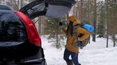 motivatie : A girl tourist after a walk through the winter forest puts her backpack in the car trunk. It is snowing outside. Slow motion. Stockvideo