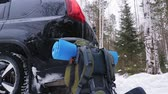 стенды : Next to the crossover, in a winter snow-covered forest, there is a traveling backpack with a mat. It is snowing outside. Slow motion.