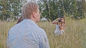 style : Adult couple posing for female photographer during fashion photo shoot outdoor