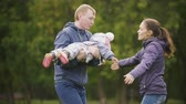 életmód : Happy family: Father, Mother and child - little girl walking in autumn park: mammy have hugs dad and baby, slow motion Stock mozgókép