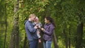 életmód : Happy family: Father, Mother and child - little girl in autumn park: dad, mammy and baby posing around Rowan