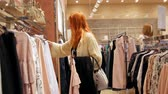 clothe : Attractive girl in a fashion dress store chose a clothe - fashion shopping