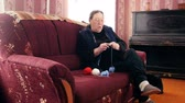 starość : Senior lady sitting on the sofa and knits colourful wool - pensioners hobby at home, slider shot Wideo