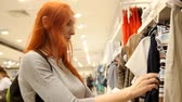 shopaholic : Woman chooses dress in a womens clothing store Stock Footage