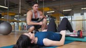 on all fours : Instructor in the gym and slim young women doing exercise for buttocks - the rise of a body lying over the bar. Slider shot Stock Footage