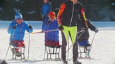 deslizamento : KAZAN, RUSSIA - March, 2018: slow motion of skiers with disabilities participating in the winter ski-race, skier passing by them Stock Footage
