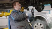 механик : Mechanic unscrews detail of car in hood - automobile service repairing, close up