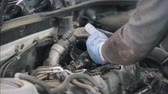 протектор : Mechanic in gloves establishing auto parts on the car Стоковые видеозаписи