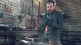 ferreiro : Craftsman blacksmith with a hammer in the workshop