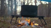 cookware : Cooking food in black boiler on the bonfire in the forest - man put in plastic trash into campfire Stock Footage