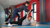 estendido : Female personal trainer help man with stretching exercise in front of mirror