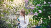 ancinho : Young girl watering cherry on a background of lilac, summer day Stock Footage
