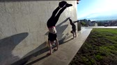 шпагат : Two female acrobat performs handstand on the wall at sunset outdoors