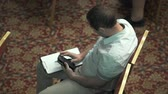 falante : Top view of man sitting with a sheet of paper and writing on the phone at the business conference Stock Footage