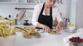 блины : Young woman pulls out of a plate freshly cooked pancakes