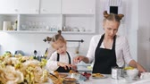 блины : Mother and her little daughter on the kitchen decorates the dessert for breakfast