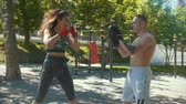 bandaj : Young man teaches beautiful woman boxing blows outdoors at sunny day, slow-motion