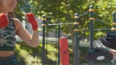bandaj : Young muscular man and woman engaged in boxing in the park ar sunny day Stok Video