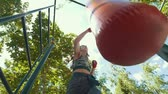 punching bag : Athletic young woman in sportswear beats a punching bag, workout in summer park - bottom view, slow-motion