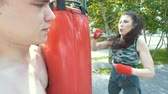 bandaj : Young man holds punching bag to athletic woman engaged in boxing in the park at sunny day, slow-motion Stok Video