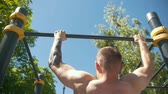 bandaj : Rear view of muscular man pulled-up on horizontal bar outdoors at sunny day
